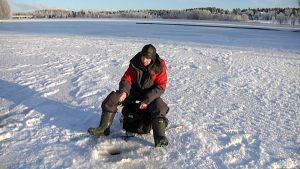 Venäläinen mies pilkkii Vuoksen rannalla Imatralla.