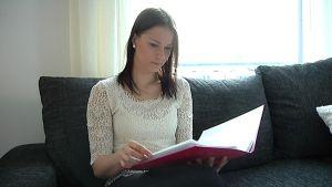 Janita Tiainen lukee sohvalla.