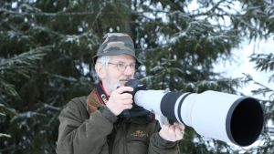 Mies kannattelee suurella objektiivilla varustettua järjestelmäkameraa.