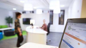 Kuvan etualalla tietokone, taustalla työnhakijan ja TE-toimiston työntekijän hahmot.