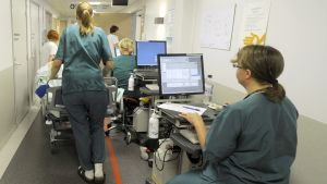 Sairaanhoitajat siirtävät potilasta sairaalan käytävällä.