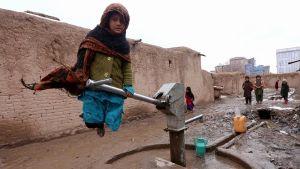Afganistanilainen tyttö täyttää vesikanisteria.