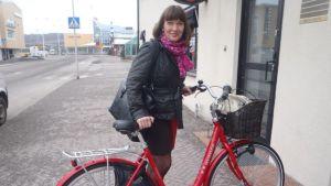 Kuvassa nainen taluttaa pyörää.