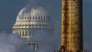 Savuinen näkymä Yhdysvaltain kongressin rakennukseen fossiilisia polttoaineita käyttävän voimalaitoksen takaa.