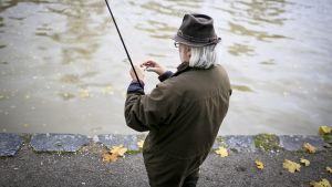 Eläkeläismies kalastaa Helsingin Vanhankaupunginlahdella.