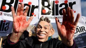 miehellä päässään naamio, nostaa verisiä käsiään mielenosoituskulkueessa