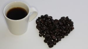 Kuvassa kahvikuppi ja paahdetuista pavuista muotoiltu sydän.