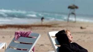 Turisti tammikuussa rannalla Havannassa.