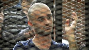 Egyptiläinen aktivisti Ahmed Doma istuu rautaverkon takana tuomioistuimessa.
