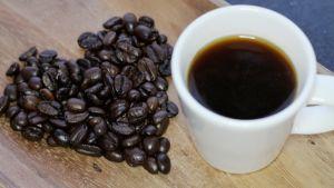 Kuvassa kupillinen kahvia ja kahvipavuista tehty sydän.