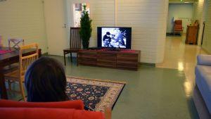 Kehitysvammainen asukas katselee televisiota kajaanilaisessa laitoskodissa.