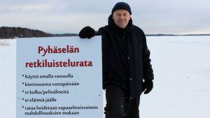 Tapio Kauppinen ja Pyhäselän retkiluisteluradan sääntökyltti.