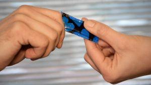 Nainen ja mies pitelevät kondomipakkausta.