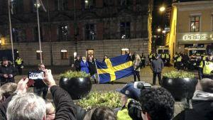 väkeä kadulla pitelee suurta Ruotsin lippua