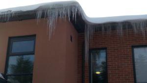 Jääpuikkoja talon räystäällä.