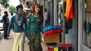 osin höyheniin pukeutunut, osin maalattu pari kävelee kadulla