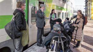 Ihmisiä pyörätuoleissa junan oven edessä.