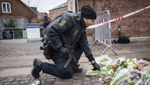 Poliisi laskee kukkia maahan.