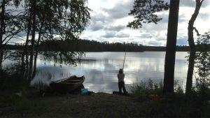 Poika kalastaa mato-ongella järven rannalla.