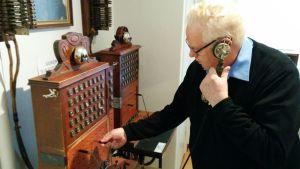 Olavi Hyvönen kokeilee vanhaa puhelinkeskusta.