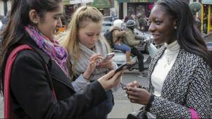 kolme tyttöä sormeilee kännykkää kadulla