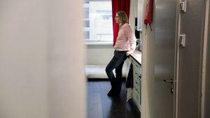 Mies seisoo asunnon keittiössä.