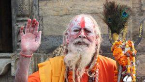 Värikkäästi pukeutunut pyhä mies poseeraa valokuvaajille. Hän pitää kädessään kolmikärkeä, joka on Shiva-jumalan symboli.