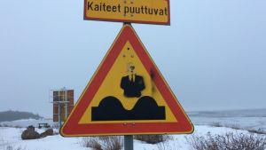 kuoppia tiellä -liikennemerkkiin on maalattu mies