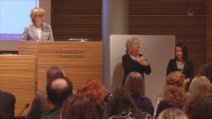 Anna Maija Henriksson puhumassa salin etuosassa.