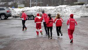 Kuusi ihmistä lähdössä yhdessä juoksulenkille.