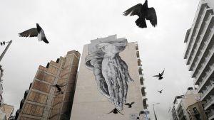 RAkennuksen seinään maalattu graffiti ja puluja Ateenan keskustassa 24. helmikuuta.