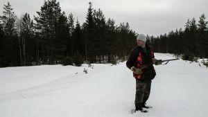 Aku Ahlholm seisoo jänispassissa lumisessa metsässä.