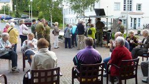Ihmisiä ulkona istumassa ja seisomassa.