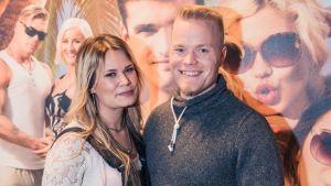 Katri Tampio ja Sami Tuomainen televisio-ohjelman julisteen edessä.