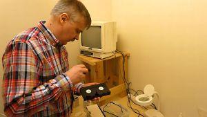 Mies avaa ruuvimeisselillä vanhaa videokasettia.