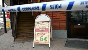 Laukaan Pizzeria Midian kyltti ja poliisin eristysnauhaa