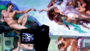 Vierailija ottaa kuvaa Michelangelon kuuluisaa maalausta esittävästä kuvasta.