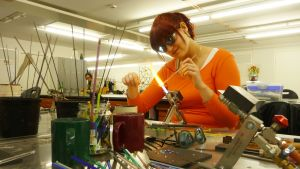 Opiskelija tekemässä lasitöitä Ikaalisissa.