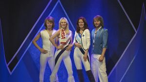 ABBA-yhtye kokonaisuudessaan kuin kultaisella 70-luvulla. Yhtyeellä on vaaleat vaatteet tummansinistä taustaa vasten.