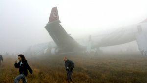 Evakuoidut matkustajat kävelevät kauemmas laskeutumisen aikana pois kiitoradalta liukuneen koneen luota Katmandun lentokentällä.