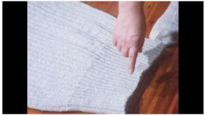 Nainen osoittaa sormella neuleen alahelmaa.