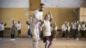 Kuva elokuvasta Miekkailija. Opettaja ohjaa oppilasta, jolla on miekka kädessä.