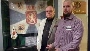 Kaksi miestä seisoo lasisen näyttelyvitriinin edessä.
