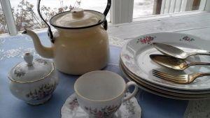Vanhoja astioita sinisellä pöytäliinalla