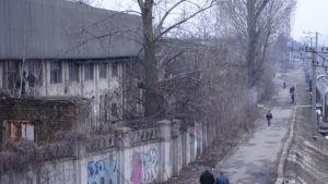 Ihmiset kävelevät hylätyn ja rapistuneen tehdasrakennuksen ohi.