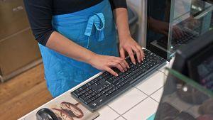 Nainen kädet näppäimistöllä leipomon kassalla.