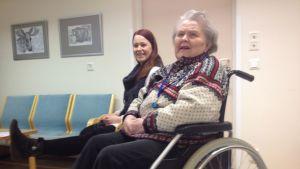 Vanha rouva istuu pyörätuolissa ja nuori nainen jumppaa istuen