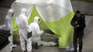 Rikostutkijoita teltalla suojattujen ruumiiden äärellä.