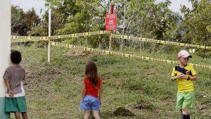 Lapset katselevat eristysaluetta, jolta raivataan miinoja.