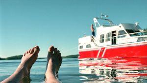 Miehen jalat veden pinnalla, taustalla punainen vene rantautuneena.
